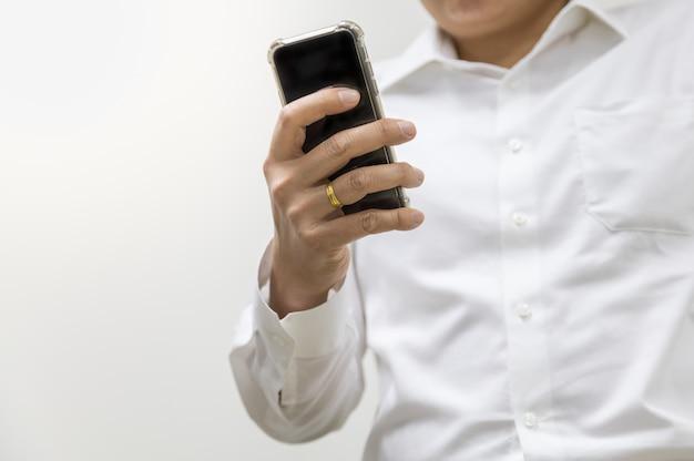 Azjatycki Biznesmen Jest Ubranym Białą Koszula Trzyma Telefon Komórkowego Na Białym Tle Z Kopii Przestrzenią. Premium Zdjęcia