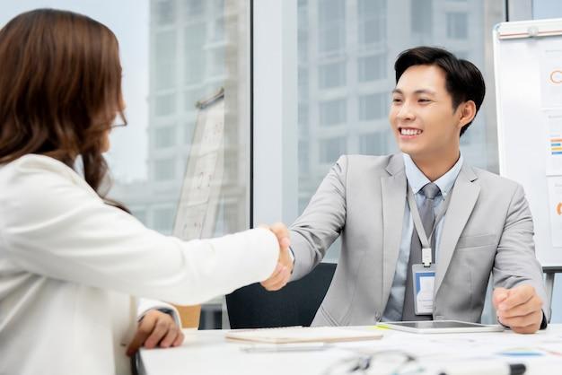 Azjatycki biznesmen robi uściskowi dłoni z bizneswomanem w biurze Premium Zdjęcia