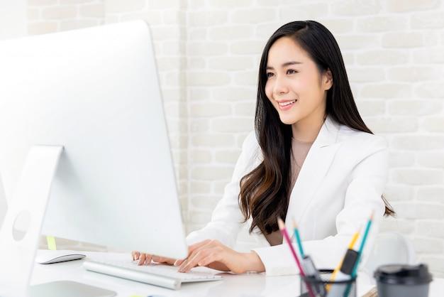 Azjatycki bizneswoman pracuje na komputerze w biurze Premium Zdjęcia