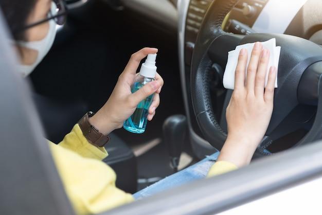 Azjatycki Bizneswoman W Zielonej Koszuli Z Maską Ochronną Przy Użyciu Dezynfekującego Sprayu Alkoholowego I Mokrej ściereczki Na Kierownicy Zapobiega Epidemicznemu Koronawirusowi Lub Koronawirusowi W Samochodzie. Premium Zdjęcia