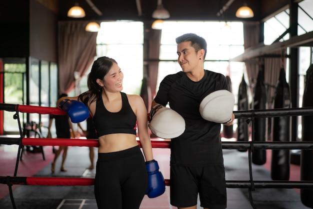 Azjatycki Bokser Bawi Się Dziewczyna I Trener Wyglądający Uśmiech Podczas Gdy Oparł Się Na Czarnych Czerwonych Linach Na Ringu Premium Zdjęcia