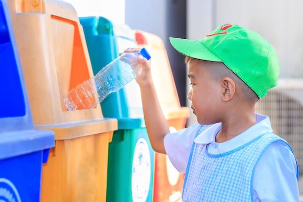 Azjatycki Chłopiec Dziecko Rzuca Plastikową Butelkę Do Kosza. Zapisz Koncepcję Ochrony środowiska. Premium Zdjęcia