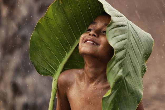 Azjatycki Chłopiec Jest Szczęśliwy, Ponieważ Bawią Się W Deszczu. Po Długiej Suszy Premium Zdjęcia