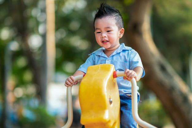 Azjatycki Chłopiec Uśmiech I Bawić Się W Boisku Premium Zdjęcia