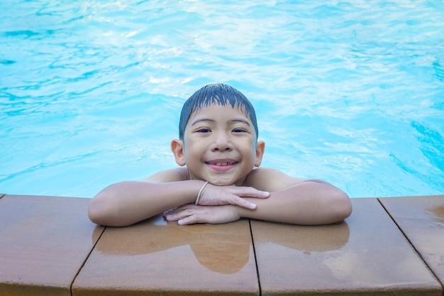 Azjatycki Chłopiec Uśmiecha Się Na Granicy Basen Niebieski Premium Zdjęcia