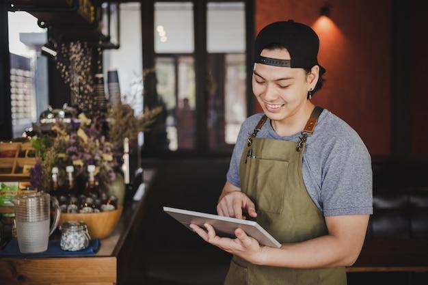 Azjatycki człowiek barista trzymając tabletkę do sprawdzania zamówienia od klienta w kawiarni kawy. Darmowe Zdjęcia