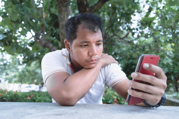Azjatycki Człowiek Czuje Się Znudzony I Smutny Moment Z Telefonem Komórkowym. Premium Zdjęcia
