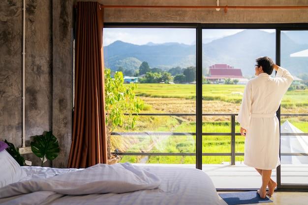 Azjatycki Człowiek Siedzieć I Zrelaksować Się Po Przebudzeniu Z łóżka Premium Zdjęcia