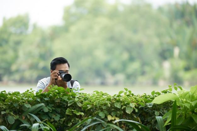 Azjatycki Człowiek Z Profesjonalnym Aparatem Wpatrując Się W Zielony żywopłot W Parku I Robienia Zdjęć Darmowe Zdjęcia