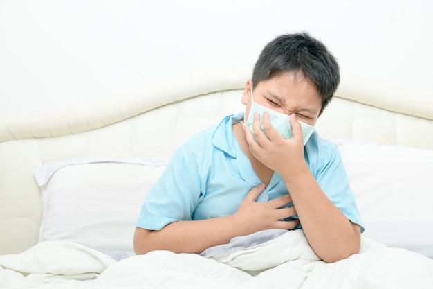 Azjatycki Gruby Chłopiec Nosi Maskę Chirurgiczną, Kaszel I Ból W Klatce Piersiowej Na łóżku, Premium Zdjęcia