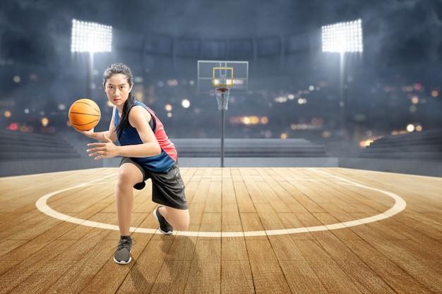 Azjatycki kobieta gracz koszykówki w akci z piłką Premium Zdjęcia