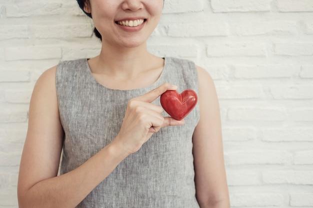 Azjatycki kobiety mienia czerwony serce, ubezpieczenie zdrowotne, darowizny dobroczynności pojęcie Premium Zdjęcia