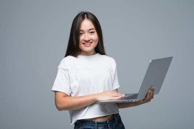 Azjatycki Kobiety Mienia Laptop Podczas Gdy Patrzejący Kamerę Nad Szarym Tłem Darmowe Zdjęcia