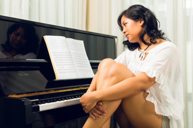 Azjatycki kobiety obsiadanie przy pianinem Premium Zdjęcia