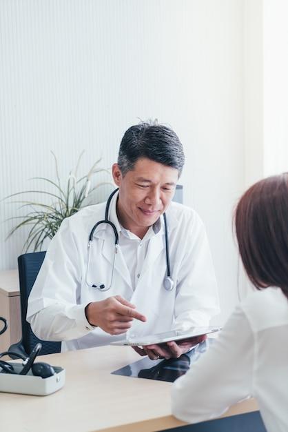 Azjatycki lekarz i pacjent dyskutują Premium Zdjęcia