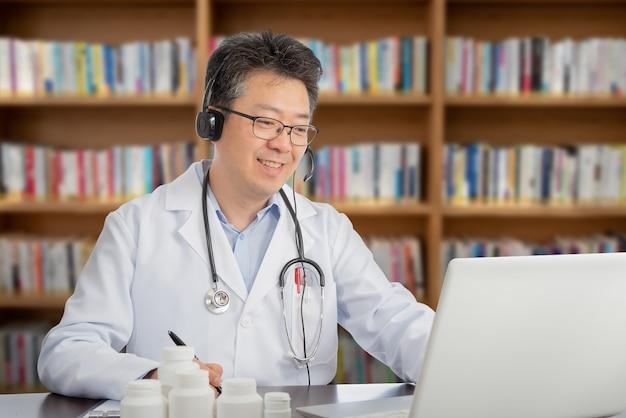 Azjatycki Lekarz, Który Zdalnie Konsultuje Się Z Pacjentem. Koncepcja Telezdrowia. Premium Zdjęcia