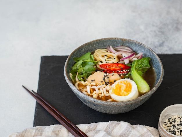 Azjatycki makaron ramen z kurczakiem, kapustą pak choi i jajkiem Premium Zdjęcia