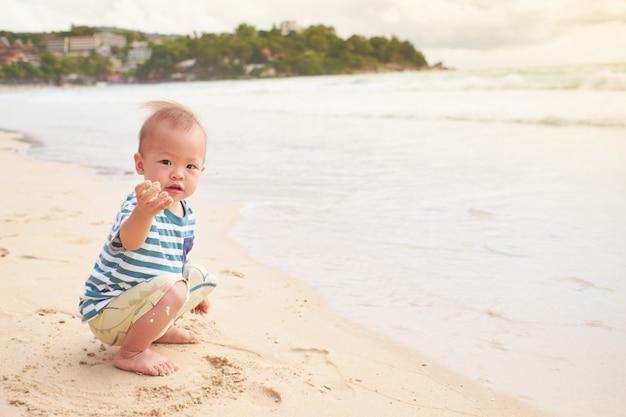 Azjatycki Maluch Chłopca Dziecko Na Plaży Z Brudnymi Rękami Pokrytymi Mokrym Piaskiem, Aktywność Na świeżym Powietrzu Podczas Letnich Wakacji Na Plaży Z Dziećmi Premium Zdjęcia