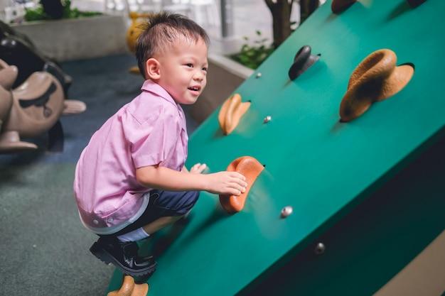 Azjatycki Maluch W Wieku 2-3 Lat Bawiący Się Wspinający Się Na Sztucznych Głazach Na Boisku Szkolnym, Mały Chłopiec Wspinający Się Po Skalnej ścianie Premium Zdjęcia