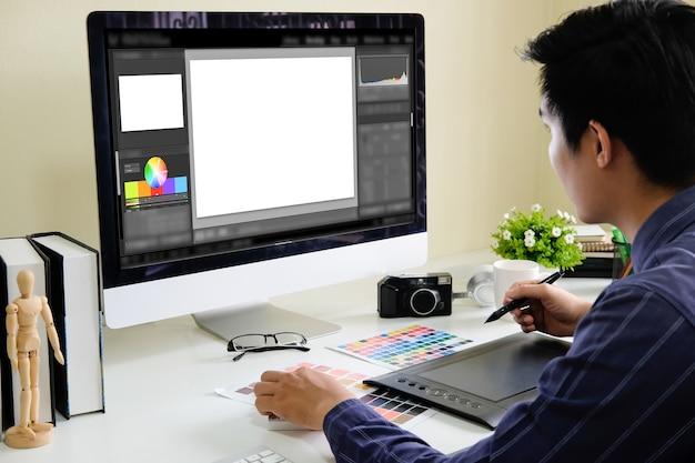 Azjatycki Męski Projektant Używa Grafiki Pastylkę Podczas Gdy Pracujący Z Komputerem Przy Studiiem Lub Biurem. Premium Zdjęcia