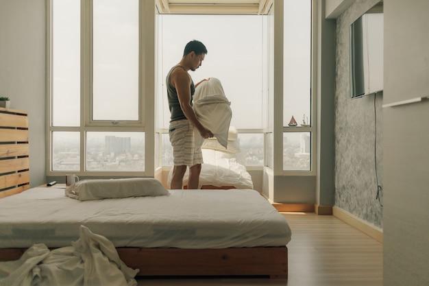 Azjatycki Mężczyzna Czyści Jego Sypialnię Z Ciepłym Letnim światłem. Premium Zdjęcia