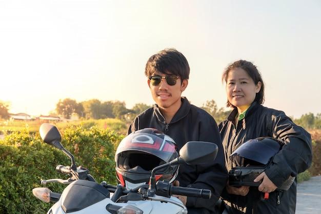 Azjatycki Mężczyzna I Kobieta W Kasku I Na Sobie I Zapiąć Przed Jazdą Duży Motocykl Na Drodze Dla Bezpieczeństwa Premium Zdjęcia