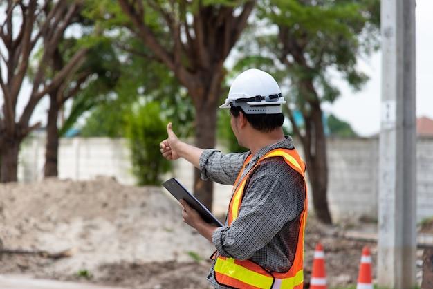 Azjatycki Mężczyzna Inżynier Budownictwa Cywilnego Lub Architekt Z Hełmem I Kamizelką Odblaskową, Pracujący I Trzymając Tablet Bezdotykowy Premium Zdjęcia