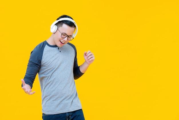Azjatycki mężczyzna jest ubranym hełmofony słucha muzyka i poruszający ciało Premium Zdjęcia