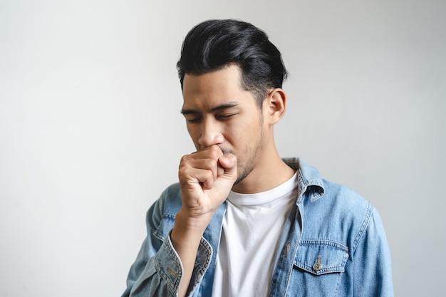 Azjatycki Mężczyzna Kasłać Odizolowywam Na Tle W Studiu. Premium Zdjęcia