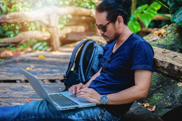 Azjatycki Mężczyzna Pracuje Fotografię Na Laptopie Przy Plenerową Naturą I Sprawdza I Jest Relaksujący Premium Zdjęcia