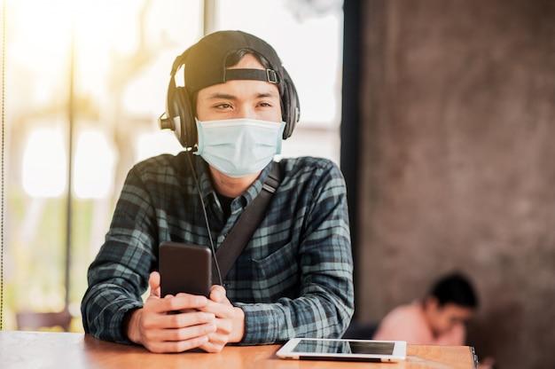 Azjatycki Mężczyzna Używa Telefonu Komórkowego W Kawiarni Wewnątrz Noszenia Maski Na Twarz Chroni Przed Wirusem Koronowym Nowy Normalny Styl życia Premium Zdjęcia