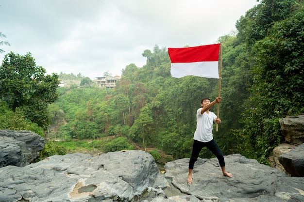 Azjatycki Mężczyzna Z Indonezyjską Flagą Indonezji Na Szczycie Góry Premium Zdjęcia