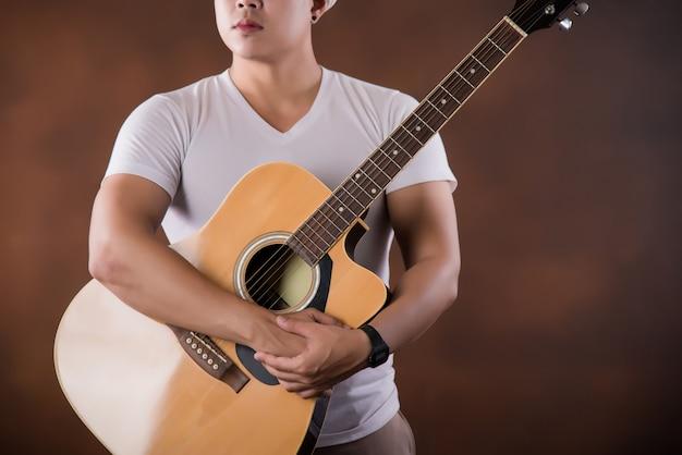 Azjatycki młody człowiek muzyk z gitarą akustyczną Darmowe Zdjęcia