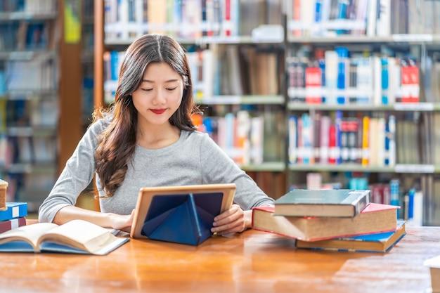 Azjatycki Młody Student W Przypadkowym Garniturze Odrabiania Lekcji I Korzystania Z Technologii Teblet W Bibliotece Uniwersytetu Premium Zdjęcia