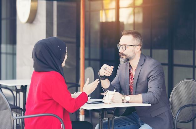 Azjatycki Muzułmański Bizneswoman W Kawiarni Rozmawia Z Klientem Lub Przyjacielem Chłopca Premium Zdjęcia