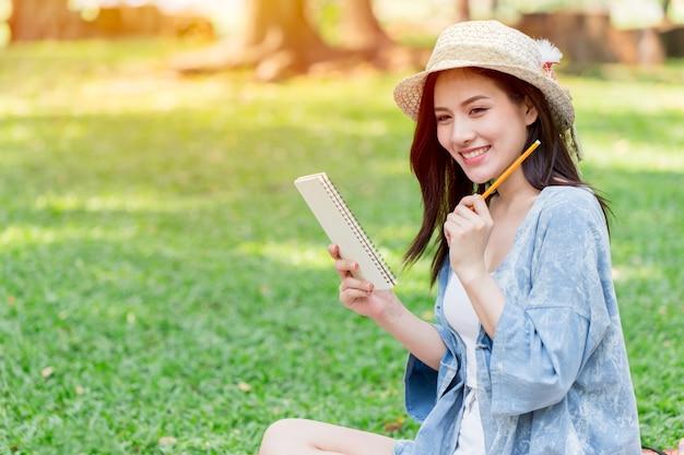 Azjatycki nastoletni uśmiech pisać pismo notatki pisma liście przy parkiem Premium Zdjęcia