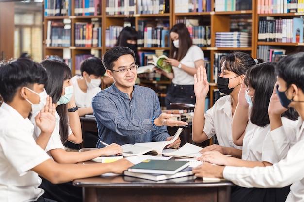 Azjatycki Nauczyciel Podnosi Rękę I Daje Lekcję Grupie Studentów Premium Zdjęcia