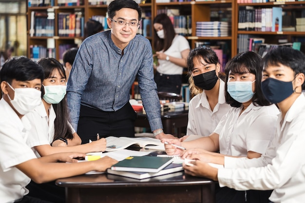 Azjatycki Nauczyciel Stojący Z Grupą Studentów W Bibliotece I Na Zajęciach Wykształcenie Uniwersyteckie Premium Zdjęcia