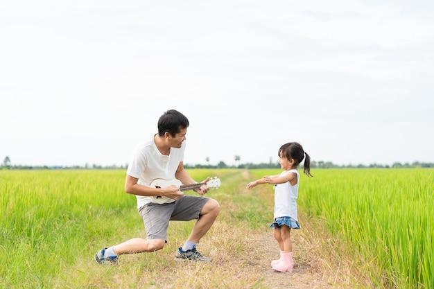 Azjatycki Ojciec I Córka Grają Ukulele I Taniec Razem W Ryżowym Polu Premium Zdjęcia