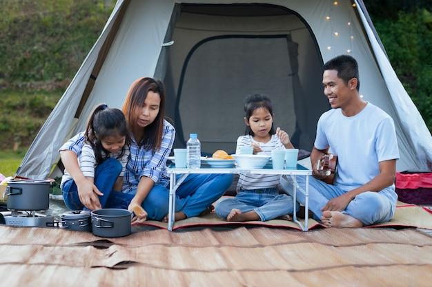 Azjatycki Ojciec, Matka I Dwie Córeczki Bawią Się Na Pikniku Przed Namiotem Na Kempingu W Pięknej Przyrodzie. Premium Zdjęcia
