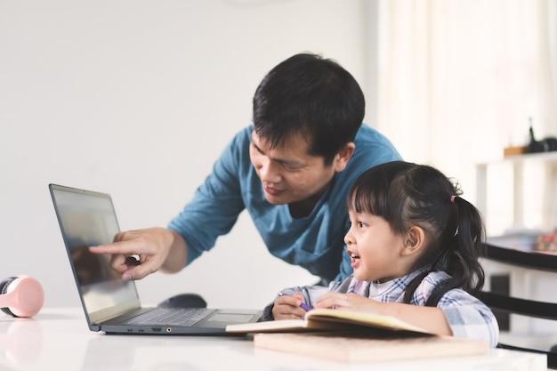 Azjatycki Ojciec Pomaga Córce W Nauce Lekcji Online. Premium Zdjęcia