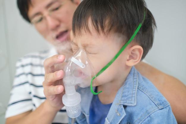 Azjatycki Ojciec Pomaga Jego Berbecia Synowi Z Inhalacyjną Terapią Maską Inhalator. Chore Małe Dziecko Z Problemami Oddechowymi Z Maską Tlenową Oddycha Przez Nebulizator Premium Zdjęcia