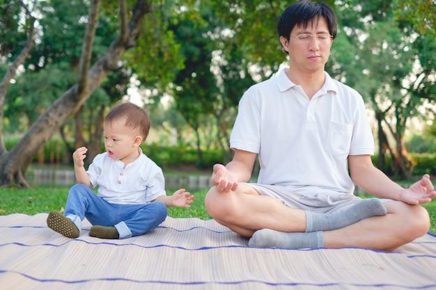 Azjatycki Ojciec Z Oczami Zamykającymi I 1 Roczniak Berbecia Chłopiec Dzieckiem ćwiczy Joga & Medytować Outdoors Na Naturze W Lecie, Zdrowy Stylu życia Pojęcie Premium Zdjęcia