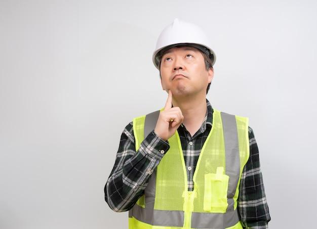 Azjatycki Pracownik W średnim Wieku, Który Dokładnie Się Nad Czymś Zastanawia. Premium Zdjęcia