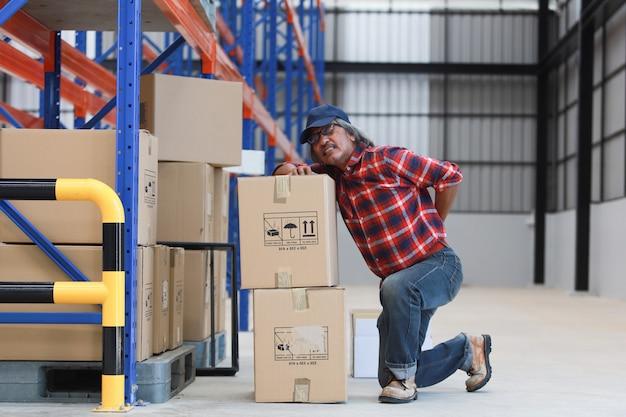Azjatycki Pracownika Mężczyzna Krzywdził Jego Tylnego Podnośnika Ciężkiego Pudełko W Fabryce Premium Zdjęcia