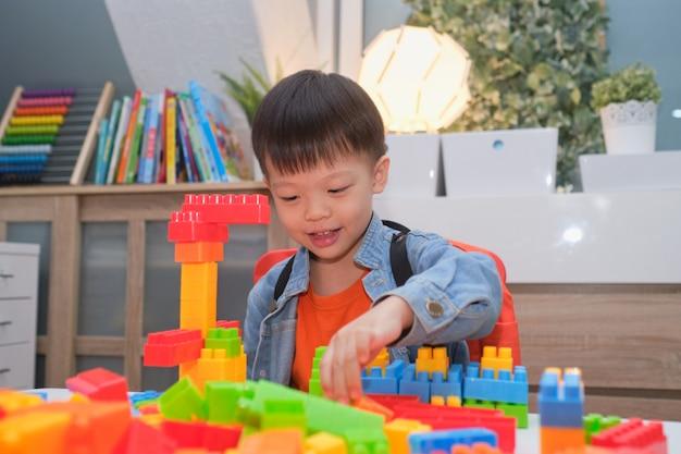 Azjatycki Przedszkolak Bawiący Się Klockami Z Kolorowymi Klockami Z Tworzywa Sztucznego W Domu, Zabawki Edukacyjne Dla Małych Dzieci, Zostań W Domu Bądź Bezpieczny Premium Zdjęcia