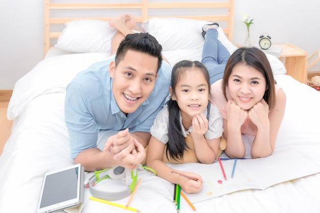 Azjatycki Rodzinny Szczęśliwy Ono Uśmiecha Się I Relaksuje Na łóżku W Domu W Wakacyjnym Wakacje. Premium Zdjęcia