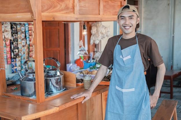 Azjatycki Sprzedawca Angkringan Mężczyzna W Fartuchu Uśmiecha Się Z Boku Stoiska Z Wózkiem Premium Zdjęcia