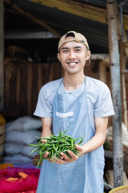Azjatycki Sprzedawca Warzyw Uśmiecha Się, Trzymając Zielone Papryczki Chili Na Straganie Warzyw Premium Zdjęcia