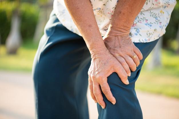 Azjatycki Starej Kobiety Odprowadzenie W Parku I Mieć Ból Kolana, Uraz Kolana W Parku Premium Zdjęcia